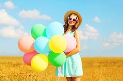 Mujer sonriente feliz con los globos coloridos de un aire que disfruta de un día de verano en un campo y un fondo del cielo azul Fotografía de archivo libre de regalías