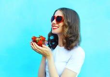 Mujer sonriente feliz con muchos fresa sobre fondo azul Fotografía de archivo libre de regalías