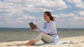 Mujer sonriente feliz con PC de la tableta en la playa del verano metrajes