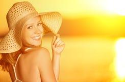 Mujer sonriente feliz de la belleza en sombrero en el mar en la puesta del sol en la playa imagen de archivo