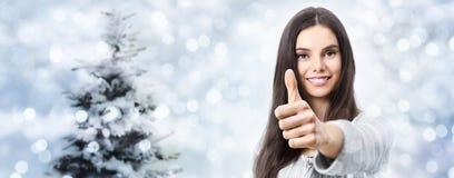 Mujer sonriente feliz de la Navidad con los pulgares para arriba, gesticulando como encendido Fotografía de archivo