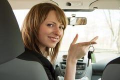 Mujer sonriente feliz del conductor que muestra la llave del coche que se sienta en un nuevo auto Foto de archivo