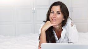 Mujer sonriente feliz del freelancer del retrato que tiene rotura que miente en cama en dormitorio delante del ordenador portátil almacen de video