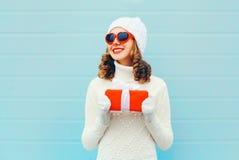 Mujer sonriente feliz del retrato de la Navidad con la caja de regalo que lleva un suéter hecho punto del sombrero sobre azul Fotos de archivo libres de regalías