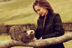 Mujer sonriente feliz del retrato del otoño que sostiene un gato imagenes de archivo