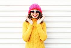 Mujer sonriente feliz del retrato que se divierte que lleva el sombrero hecho punto colorido Foto de archivo