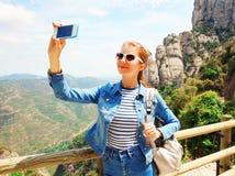 Mujer sonriente feliz del viaje que toma el selfie de la imagen en el smartphone Imagenes de archivo
