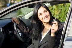 Mujer sonriente feliz dentro del coche que muestra llaves Fotos de archivo libres de regalías