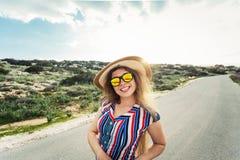 Mujer sonriente feliz el vacaciones con el sombrero y los vidrios del sol Imágenes de archivo libres de regalías