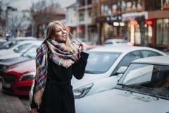 Mujer sonriente feliz en capa y bufanda negras muchacha que camina alrededor de ciudad foto de archivo libre de regalías