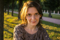 Mujer sonriente feliz en el parque en verano trasero de oro de la puesta del sol de la iluminación Foto de archivo libre de regalías