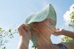 Mujer sonriente feliz en sombrero en un día soleado en el parque Foto de archivo