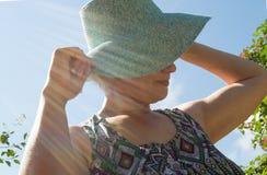 Mujer sonriente feliz en sombrero en un día soleado en el parque Imagen de archivo