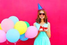 Mujer sonriente feliz en un casquillo del cumpleaños con una caja de regalo en las manos, globos coloridos de un aire sobre fondo Fotografía de archivo libre de regalías