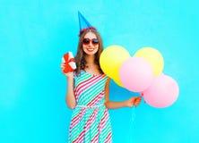 Mujer sonriente feliz en un casquillo del cumpleaños con una caja de regalo en las manos, globos coloridos de un aire sobre fondo Imagenes de archivo