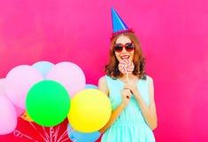 Mujer sonriente feliz en un casquillo del cumpleaños con una piruleta en el palillo sobre los globos coloridos de un aire en fond Fotografía de archivo