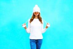 Mujer sonriente feliz en un sombrero hecho punto, suéter en un azul Imagenes de archivo