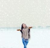 Mujer sonriente feliz hermosa de la muchacha que camina en un campo en una tarde del invierno, y nieve feliz Foto de archivo
