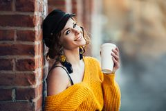 Mujer sonriente feliz hermosa que sostiene la taza de café plástica de papel al aire libre en parque de la calle de la ciudad en  imagen de archivo