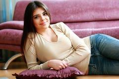 Mujer sonriente feliz joven que miente en el piso Imagen de archivo