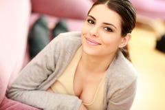 Mujer sonriente feliz joven que miente en el sofá Imagen de archivo libre de regalías