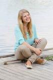Mujer sonriente feliz joven que se sienta en el embarcadero y la sonrisa Fotos de archivo