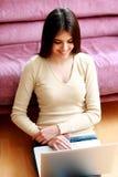 Mujer sonriente feliz joven que se sienta en el piso y que usa el ordenador portátil Imagenes de archivo