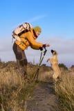 Mujer sonriente feliz que camina en montañas con el perro Fotos de archivo