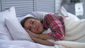 Mujer sonriente feliz que despierta en su dormitorio almacen de metraje de vídeo