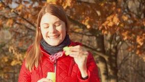 Mujer sonriente feliz que disfruta de la naturaleza Colocación en parque del otoño Hembra en la capa roja que hace burbujas de ja almacen de metraje de vídeo