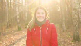 Mujer sonriente feliz que disfruta de la naturaleza Colocación en parque del otoño Sonrisa bastante femenina de los jóvenes en la almacen de video