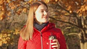 Mujer sonriente feliz que disfruta de la naturaleza Hembra joven en capa roja con la taza caliente que se coloca en parque del ot almacen de video