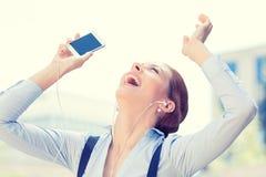 Mujer sonriente feliz que escucha la música con los auriculares Fotografía de archivo