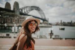 Mujer sonriente feliz que explora Sydney, con el puente del puerto en el fondo imagenes de archivo