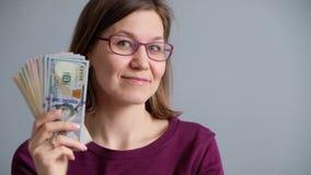 Mujer sonriente feliz que lleva a cabo paquetes de los dólares almacen de metraje de vídeo
