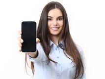 Mujer sonriente feliz que muestra el teléfono móvil aislado en blanco fotografía de archivo libre de regalías