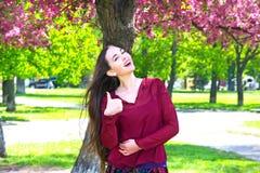 Mujer sonriente feliz que se coloca delante del árbol de Sakura y que muestra MUY BIEN Fotografía de archivo libre de regalías