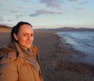 Mujer sonriente feliz que se coloca en una playa Fotos de archivo