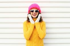 Mujer sonriente feliz que se divierte que lleva el sombrero rosado hecho punto colorido sobre blanco Foto de archivo
