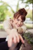 Mujer sonriente feliz que se relaja en un banco de parque Fotos de archivo libres de regalías