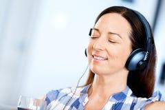 Mujer sonriente feliz que se relaja y que escucha la música Imagen de archivo libre de regalías