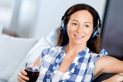 Mujer sonriente feliz que se relaja y que escucha la música Fotos de archivo libres de regalías