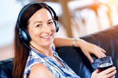 Mujer sonriente feliz que se relaja y que escucha la música Foto de archivo