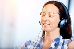 Mujer sonriente feliz que se relaja y que escucha la música Imagen de archivo
