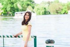 Mujer sonriente feliz que se sienta en el parque por el lago Fotos de archivo libres de regalías