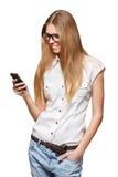 Mujer sonriente feliz que sostiene un teléfono móvil mientras que envío de mensajes de texto aislado en blanco Foto de archivo