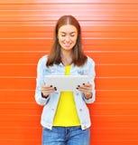Mujer sonriente feliz que usa el ordenador de la PC de la tableta en ciudad sobre naranja Fotografía de archivo libre de regalías