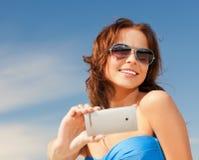 Mujer sonriente feliz que usa la cámara del teléfono Fotos de archivo libres de regalías