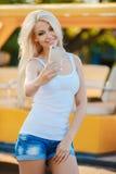 Mujer sonriente feliz que usa su teléfono en la ciudad Imágenes de archivo libres de regalías