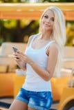 Mujer sonriente feliz que usa su teléfono en la ciudad Fotos de archivo libres de regalías